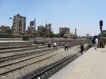 Pedestrians cross tracks at Ramses Station platform.